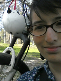 Me in front of my bike, with blossoming cherry trees in the background.